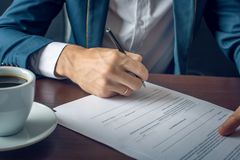 Affärsmannen undertecknar viktiga lagliga dokument på skrivbordet med koppen kaffe Royaltyfri Foto