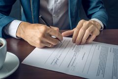 Affärsmannen undertecknar viktiga lagliga dokument på skrivbordet med koppen kaffe Royaltyfria Bilder