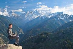 Affärsmannen upptill av berget genom att använda hans bärbar dator Arkivfoto