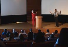 Affärsmannen visade hans presentation på etapp framme av åhörare i salongen royaltyfria bilder