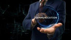 Affärsmannen visar begreppshologrammet Communiccation på hans hand royaltyfri foto