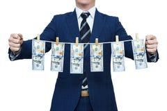 Affärsmannen visar tvättade pengar Affärsman som rymmer pengar som hänger på ett rep fotografering för bildbyråer