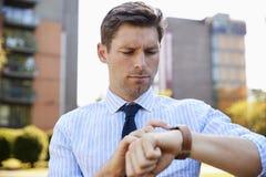 Affärsmannen Walking Through City parkerar att se den smarta klockan arkivfoton