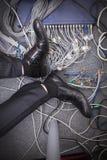 Affärsmannens fot på jordningen som omges av datoren, kablar fotografering för bildbyråer