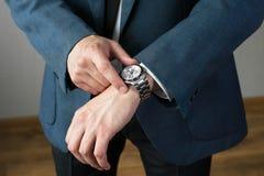 Affärsmannens foto i en dräkt En hand med timmar Royaltyfria Foton