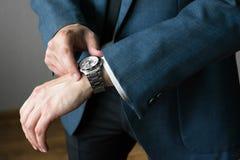 Affärsmannens foto i en dräkt En hand med timmar Arkivbilder