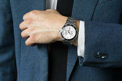 Affärsmannens foto i en dräkt En hand med timmar Arkivfoto