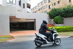 Affärsmanpendling som arbetar i regnet på bärande helment för motorisk sparkcykel och jumpsuit- och bäradatorpåse längs belevad s royaltyfri fotografi