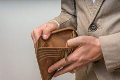 Affärsmanperson som rymmer en tom plånbok, inga pengar royaltyfria foton