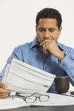 AffärsmanReading Document In kontor royaltyfri bild