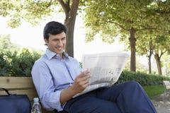 AffärsmanReading Newspaper On bänk royaltyfria bilder