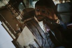 Affärsmansammanträde i bilen och innehavet hans solglasögon royaltyfria bilder