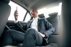 Affärsmansammanträde i bilen som ser hans mobiltelefon royaltyfri bild