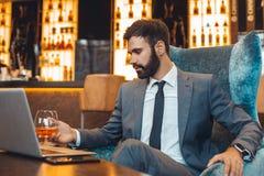 Affärsmansammanträde i en stång för affärsmitt som dricker att tänka arkivfoton
