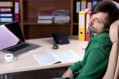 Affärsmansammanträde i stol på att tänka för kontorsskrivbord arkivfoton
