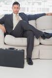 Affärsmansammanträde med ben korsade på soffan Arkivbild