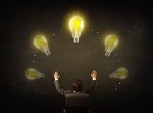 Affärsmansammanträde med lightbulbs över hans huvud Arkivbild