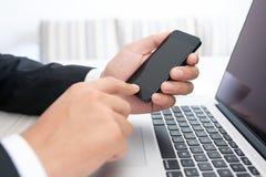 Affärsmansammanträde på en bärbar dator med telefonen Arkivfoton