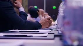 Affärsmansammanträde på en tabell och ett innehav en penna materiel Affärsman med en penna på konferensen Royaltyfri Foto