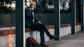 Affärsmansammanträde som talar utomhus över mobiltelefonen royaltyfria foton