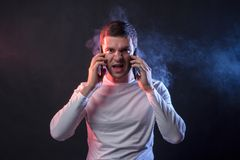 Affärsmansamtal på två telefoner och skrin från överansträngning och arkivfoto