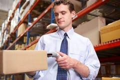 Affärsmanscanningen paketerar i lager Arkivfoton