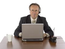 affärsmanskrivbordhörlurar med mikrofon arkivbild