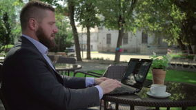 Affärsmanslut arbetar efter läs- dåliga nyheter på bärbara datorn som är utomhus- steadicamskott stock video