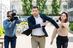 affärsmanspring från journalister med den digitala videokameran royaltyfria bilder
