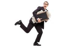 Affärsmanspring med en påse som är full av pengar Arkivbilder