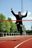 Affärsmanspring på det idrotts- spåret som firar seger i arbetsframgångbegrepp Arkivbilder