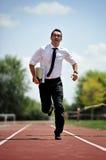 Affärsmanspring som är snabb på idrotts- spår i arbetsspänning och angelägenhetbegrepp Arkivfoto