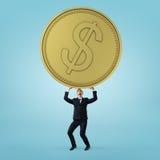 Affärsmanställningar och hållande skurkroll, stort guld- mynt på blå bakgrund Royaltyfria Foton