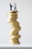 Affärsmanstå och hand som kontrollerar på riskabel myntbunt Fotografering för Bildbyråer