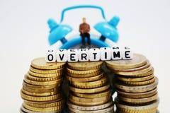Affärsmanstatyetten med bärbar datorsammanträde på klassikerblått tar tid på, bak högarna av kontanta pengar som betalas övertids Royaltyfri Fotografi