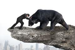 Affärsmanstridighet mot svart björn på klippan med himmelcitysc Arkivfoton