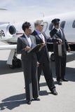 AffärsmanTaking Briefcase From chaufför At Airfield Royaltyfri Bild
