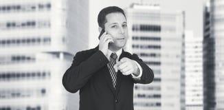 AffärsmanTalking On The telefon och företags byggnader för peka pekfinger in mot kamera med affärsstaden och i bakgrund royaltyfria bilder