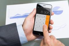 AffärsmanUsing Calculator On Apple iPhone 6 på tabellen Arkivfoton