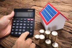 AffärsmanUsing Calculator By mynt och sol- modell Home royaltyfria bilder