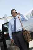 AffärsmanUsing Cellphone At flygfält Arkivbild