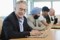 AffärsmanUsing Laptop Besides multietniska kollegor Royaltyfria Bilder