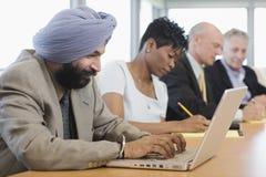 AffärsmanUsing Laptop Besides multietniska kollegor Arkivbild