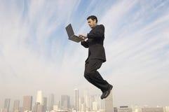 AffärsmanUsing Laptop In Midair med Cityscape i bakgrund arkivfoton
