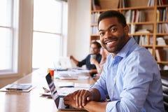 AffärsmanUsing Laptop At skrivbord i upptaget kontor Arkivfoton