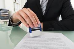 AffärsmanUsing Stamper On dokument arkivfoto