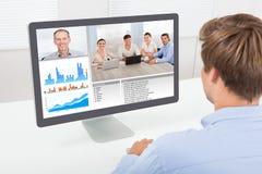 Affärsmanvideoconferencing på datoren Arkivbild