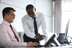 Affärsmanvisning något till den manliga kollegan på bärbara datorn på kontorsskrivbordet Arkivfoto