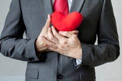 Affärsmanvisningmedkänsla som rymmer röd hjärta på hans bröstkorg Royaltyfri Foto