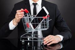 AffärsmanWith Shopping Cart modell And Mobile Phone på skrivbordet Arkivbilder
